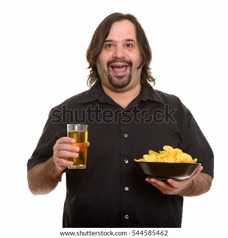 Happy fat Caucasian man smiling while holding bowl of chips and glass of beer isolated against white background