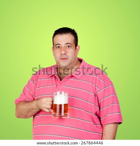 Happy fat man drinking a beer and a green background