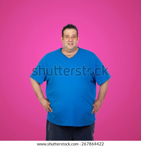 Happy fat man with blue shirt and a pink background - stock photo
