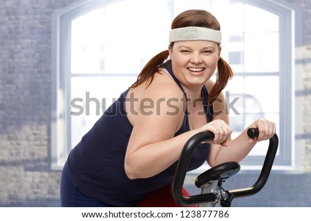 Happy fat woman training on exercise bike, smiling. - stock photo