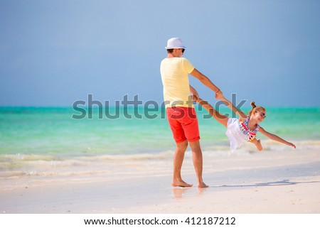 Happy father and adorable little daughter at tropical beach having fun - stock photo