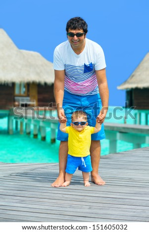 Happy Father and baby boy having fun on Maldives, walking on the bridge to water villas - stock photo