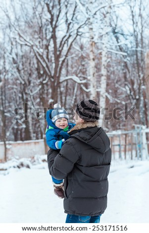 Happy father and baby playing on snow in winter park - stock photo