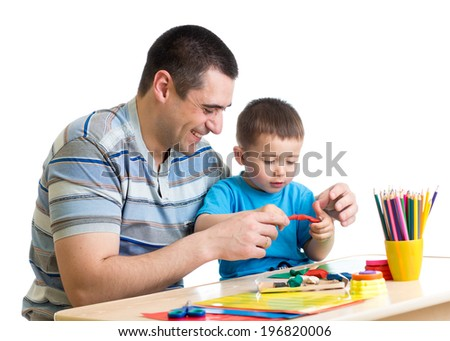 Happy father and child boy play clay together - stock photo