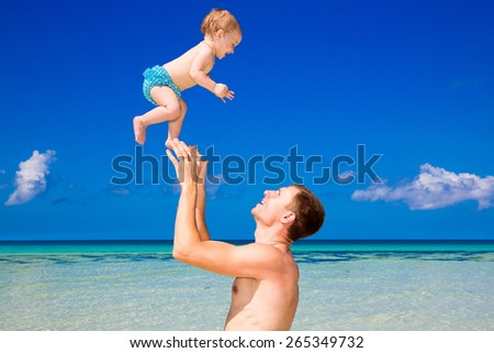 Happy father and child having fun on a tropical beach. Summer vacation concept. Outdoor portrait of a happy family. - stock photo