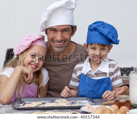 Happy father and children baking cookies together in the kitchen - stock photo