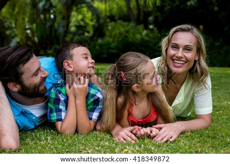 Happy father and children looking at smiling mother while lying in yard - stock photo