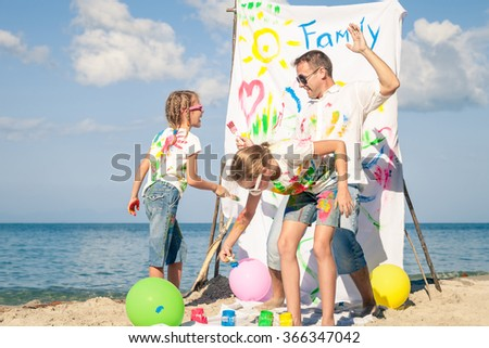 Happy father and children playing with paint on the beach at the day time. Concept of friendly family.
