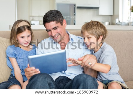 Happy father and children using digital tablet while sitting on sofa at home - stock photo