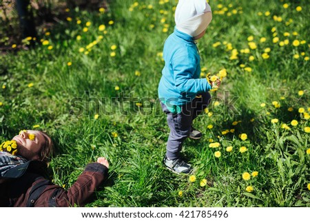 Happy father and cute little baby have good time in nature in sunny spring day. Happy family concept