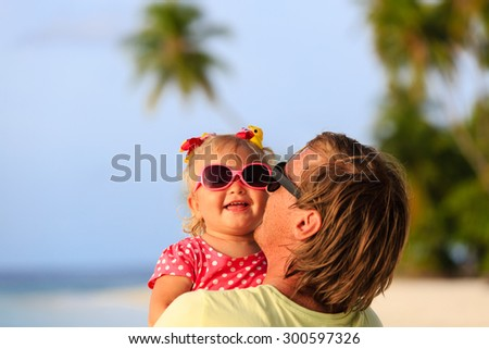 Happy father and cute little daughter at beach, family care