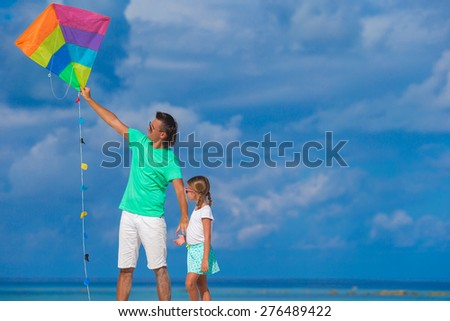 Happy father and cute little daughter flying kite together at tropical beach - stock photo