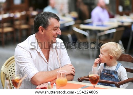 Happy father and daughter, cute little baby girl, having fun together in Italian cafe sitting at table on outdoor terrace on a warm summer day waiting for dinner drinking refreshing ice tea and juice - stock photo