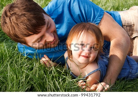 Happy Father And Daughter Laying In Grass - stock photo