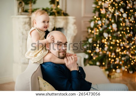 Happy father and daughter on a background of Christmas tree - stock photo