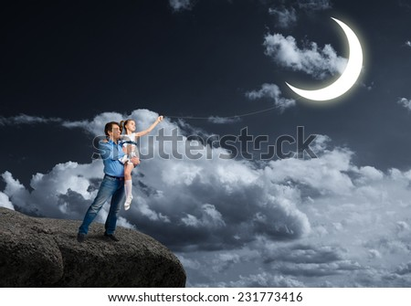 Happy father and daughter outdoor with moon on rope - stock photo