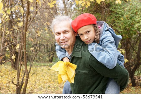 Happy father and daughter playing in autumn park - stock photo