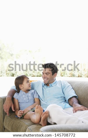 Happy father and daughter relaxing on sofa at home - stock photo