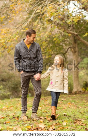 Happy father and daughter walking together in park on an autumns day - stock photo