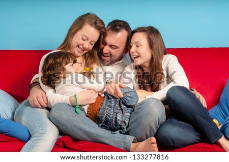 happy father and daughters on the couch in the living room