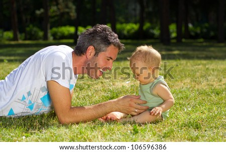 Happy father and his baby son having fun in the park. - stock photo