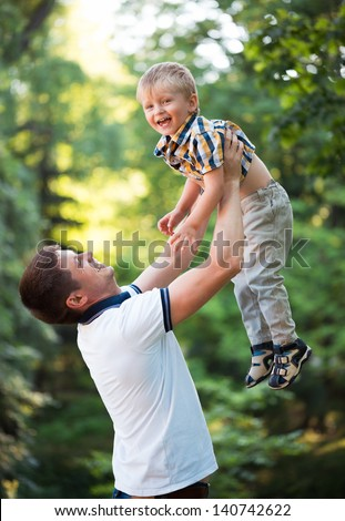 Happy father and his baby son having fun in the park outdoor