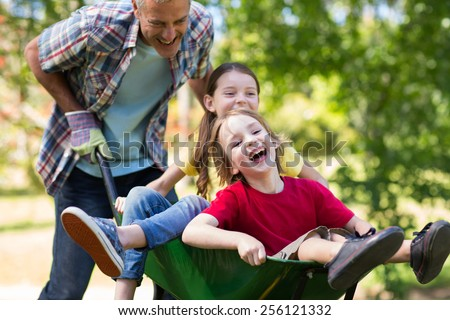 Happy father and his children playing with a wheelbarrow on a sunny day - stock photo
