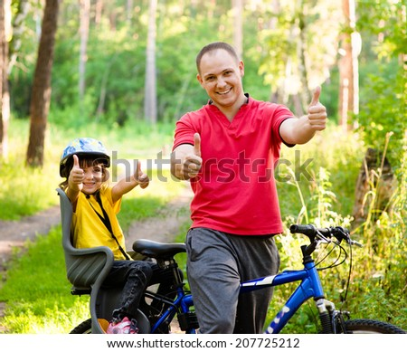 happy father and his cute daughter outdoors in forest on a bike showing thumbs up
