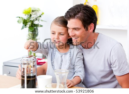 Happy father and his daughter having breakfast together in the kitchen - stock photo