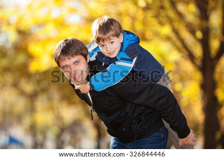 Happy father and his son in the autumn park - stock photo