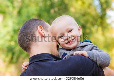 Happy father and his son outdoors. Child hugging daddy and looking out behind his back - stock photo