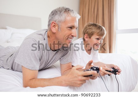Happy father and his son playing video games in a bedroom - stock photo