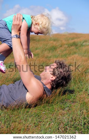 Happy father and his toddler daughter enjoying summer time at the grass meadow  - stock photo
