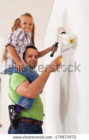 Happy father and little girl painting the room together - having fun with paint rollers - stock photo