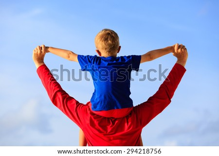 happy father and little son on shoulders play on sky - stock photo