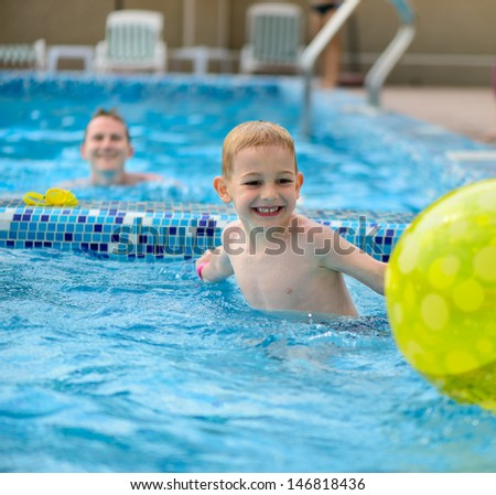 Happy father and little son playing with ball in swimming pool - stock photo