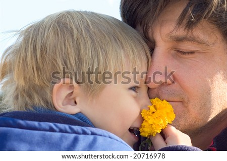 happy father and little son with flower outdoor closeup - stock photo
