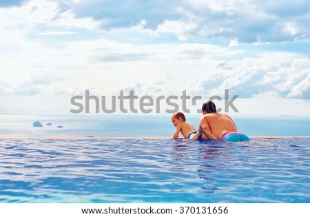 happy father and son enjoy beautiful seascape from infinity pool, vacation concept - stock photo