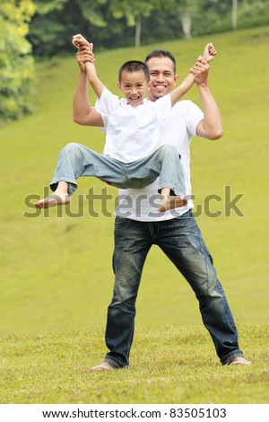 Happy father and son having fun together in the park - stock photo