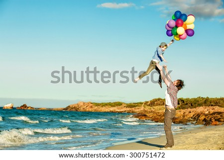 Happy father and son having quality family time on the beach playing with balloons on summer holidays. Lifestyle, vacation, happiness concept - stock photo