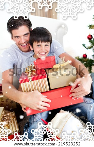 Happy father and son holding Christmas presents against snow falling