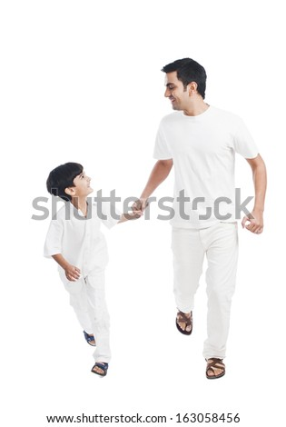 Happy father and son holding hands - stock photo