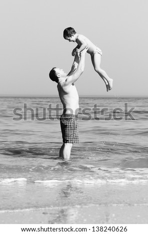 Happy father and son on the beach. black and white photo. - stock photo