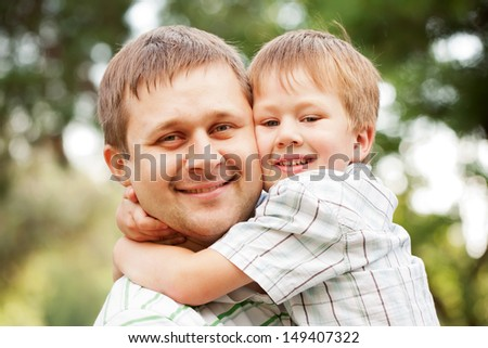Happy father and son outdoors.  Child hugging daddy. - stock photo
