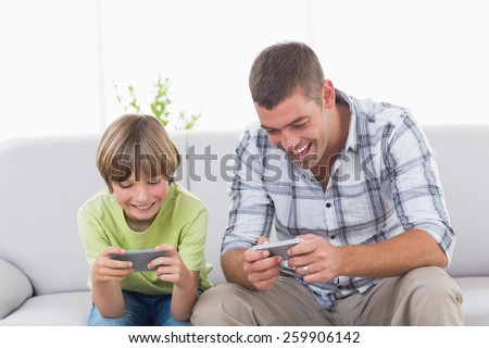 Happy father and son playing games on mobile phone at home - stock photo