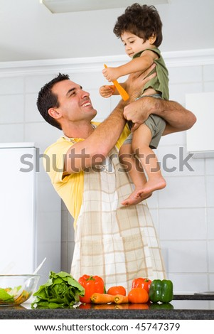 happy father and son playing in modern kitchen - stock photo