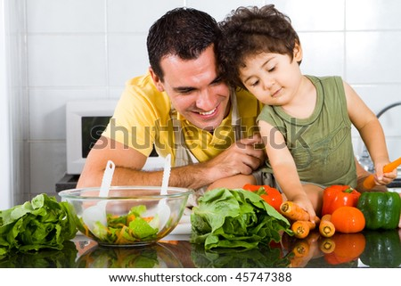 happy father and son playing in modern kitchen, son is sitting on kitchen counter