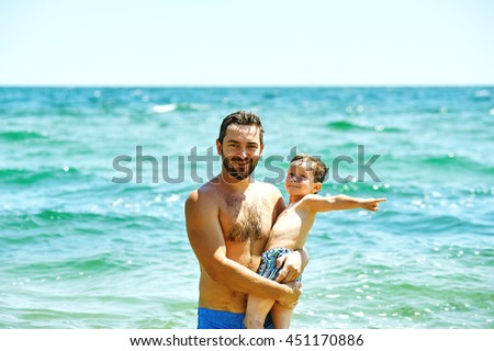 happy father and son playing in the sea