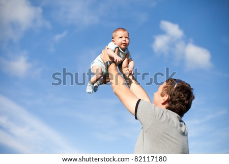 happy father and son playing on sky background