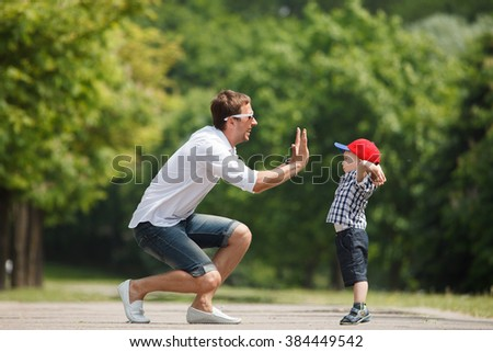 Happy father and son playing together having fun in the summer park on a warm sunny day. Family and love concept. - stock photo